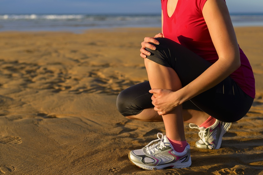 Woman with shin splints on the beach